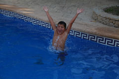 A boy is jumping into a swimming pool. You can have so much fun splashing and playing in the swimming pool in hot weather of spanish summer Royalty Free Stock Images