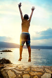 Boy jumping and taking a deep breath at the sunset Stock Image