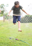 Boy jumping thru sprinkler. Barefoot little boy - smiling kid jumping thru splashing sprinkler and soaking wet royalty free stock photography