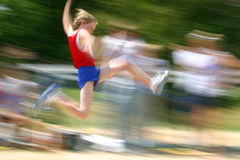 Boy jumping at track meet /motion blur. Motion blur of boy jumping at a track and field competition royalty free stock photo