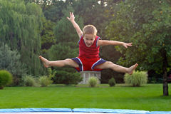 Boy Jumping on trampoline. Doing splits Royalty Free Stock Photos