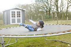 Boy jumping on trampoline Stock Photo