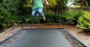 Boy jumping up and down on bouncing trampoline 4k. Boy jumping up and down on bouncing trampoline in garden 4k stock video footage