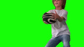 Boy jumping up to catch rugby ball on green screen close up stock footage