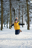 Boy jumping up in the winter forest Royalty Free Stock Photo