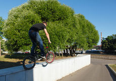 Boy jumping from wall on bmx. Summer early morning sunny weather clear sky Royalty Free Stock Image