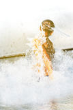 Boy jumping from water with splashes Stock Photography