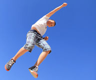 Boy jumps. Boy jumping against the blue sky Royalty Free Stock Images