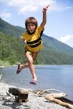 Boy jumps. On beach beside lake Stock Photography