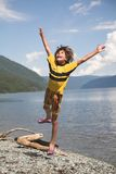 Boy jumps. On beach beside lake Royalty Free Stock Photography