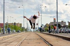 Boy jumps backflip on tramlines in the city Stock Images