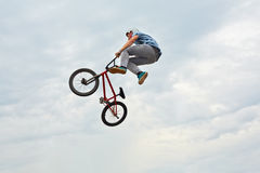 Boy jumps on bike. MOSCOW - AUG 4: Boy jumps on bike at All-Russian Exhibition Centre during holiday dedicated to 73d birthday of country main exhibition, August Royalty Free Stock Images