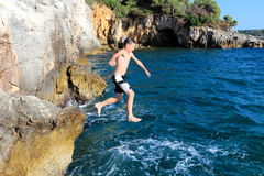 Boy jumps from cliff. In the ocean Royalty Free Stock Image
