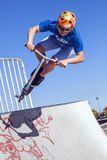 Boy jumps with his scooter over a ramp at a skatepark Royalty Free Stock Images