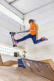 Boy jumps with his scooter in a skate hall Royalty Free Stock Photos
