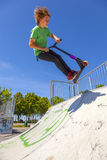 Boy jumps with his scooter at a skate park Royalty Free Stock Photography