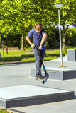 Boy jumps with his scooter at a skate park Royalty Free Stock Image