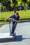 Boy jumps with his scooter at a skate park Stock Photos