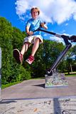 Boy jumps with his scooter in the skatepark Royalty Free Stock Photos