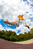 Boy jumps with his scooter in the skatepark Royalty Free Stock Photography