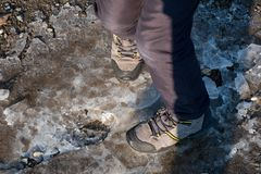 A boy jumps with his winter shoes on the icy puddle until it breaks and shatters stock photos