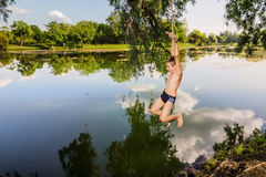 A boy jumps in a lake with a bungee jumping Royalty Free Stock Photography
