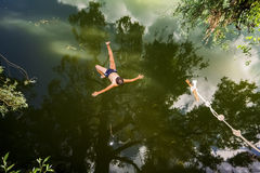 A boy jumps in a lake with a bungee jumping Royalty Free Stock Image