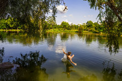 A boy jumps in a lake with a bungee jumping Royalty Free Stock Photo