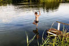 A boy jumps in a lake with a running start Royalty Free Stock Photo