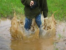 A boy jumps into a muddy puddle royalty free stock photos
