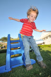 Boy jumps off a slide onto the grass stock images