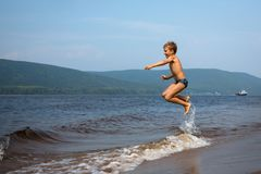 The boy jumps over the waves on the beach.Sunny summer day stock photography