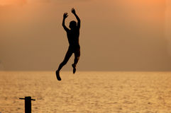 Boy jumps from pierce Royalty Free Stock Image