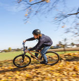 Boy jumps rides his bicycle with speed in open area and enjoys r Royalty Free Stock Photography