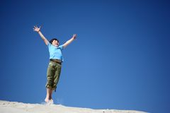 Boy jumps on sand with  lifted hands Stock Photos