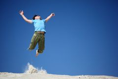 Boy jumps on sand with  lifted hands Stock Photography