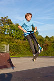 Boy jumps with scooter at the skate Royalty Free Stock Image