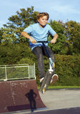Boy jumps with scooter at the skate park over a ramp Royalty Free Stock Images