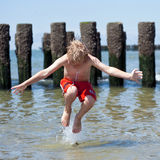 Boy jumps in sea Stock Images