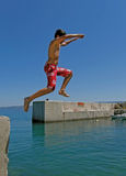 Boy jumping in sea. One alone boy jump ( in red swim wear )  into the Adriatic  sea from old port at summer holidays at Dalmatia (Croatia). Vertical color photo Stock Photos