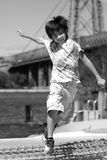 A boy jumps smiling. A multi ethnic boy smiles while jumping on the banks fo the East river Royalty Free Stock Images