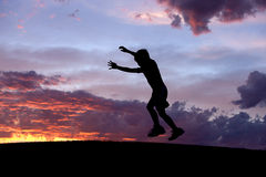 Boy jumps at sunset. Stock Photo