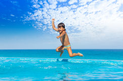 Boy jumps in swimming pool with seaside background. Boy jumping in swimming pool in excitement with seashore background Royalty Free Stock Image