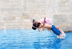 Boy jumps in the swimming pool with sister Stock Image