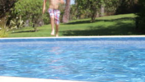 Boy Jumps Into Swimming Pool Then Swims Across Pool Royalty Free Stock Image