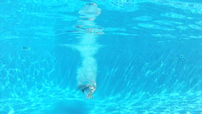 Boy Jumps Into Swimming Pool Then Swims Underwater To Camera stock video footage