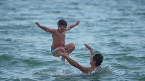 A boy jumps into the water with his father`s shoulders slow motion video stock video footage