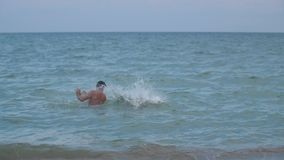 A boy jumps into the water from his father`s shoulders Slow motion video stock footage