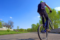 Boy jums on bike's wheel Stock Images
