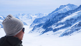 Boy is on the Jungfrau top of Europe with snow mountain background Royalty Free Stock Photography